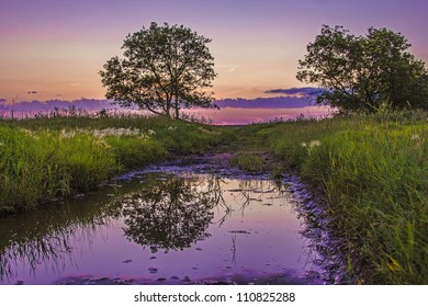 A dramatic and colorful sky reflecting in a small pool of water on a country road.