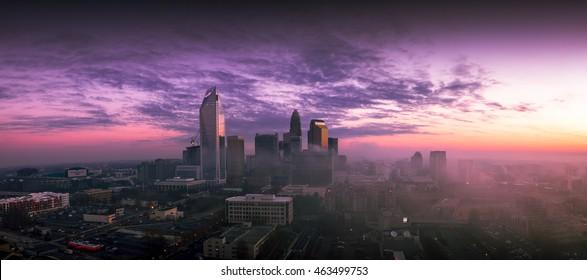 A dramatic and colorful sunrise of the Charlotte, North Carolina skyline from the rooftop of a residential building.