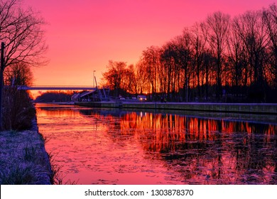 Dramatic and colorful sunrise over a Beautiful early winter landscape with a frozen river or canal, treelined riverside and grass at sunrise creating a tranquile and quiet scenic nature background