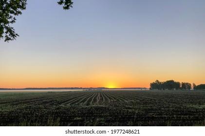 Dramatic and colorful sunrise sky. Dramatic and colorful sunrise or sunset sky over a grassy green farmfield