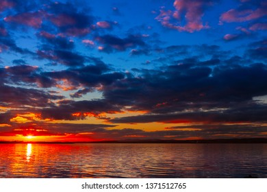 Dramatic colorful vibrant sunset sky with clouds reflected in the water.