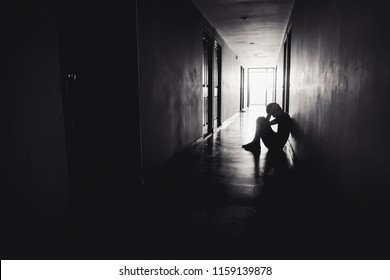 dramatic concept, Silhouette of Sad Depressed man sitting head in hands on the floor.