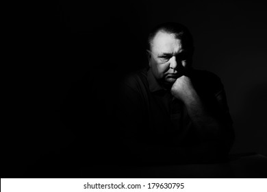 Dramatic contrast black & white portrait of thoughtful middle aged man with hand under chin