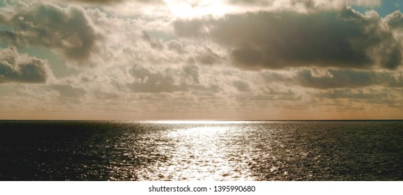 Dramatic and contrasty cloudscape and sun reflected in the water, seascape and cloudscape seen from the a high coast of an island.