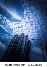 Dramatic Cumulous Clouds over the Modern Building and a Street Lamp in Silhouette