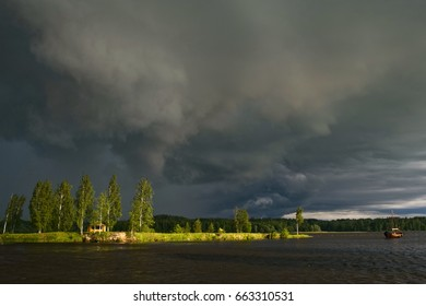 Dramatic dark rain storm sky cloud over the bower summerhouse on the green grass and trees island in river water in summer evening sun light
