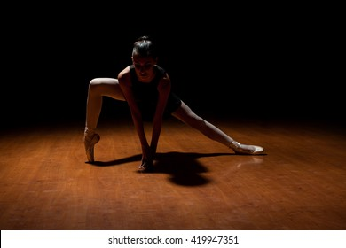 Dramatic dark scene of a beautiful female ballet dancer performing alone in a stage with a spotlight