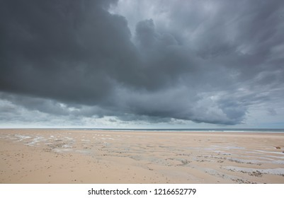 Dramatic dark storm clouds bringing heavy rain to wide open deserted sandy Normandy beaches in France in Europe