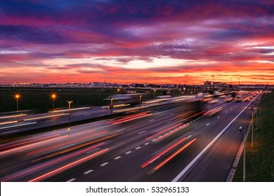 A dramatic dawn sky near the Brussels Airport, Belgium, with cars passing by and motion blur