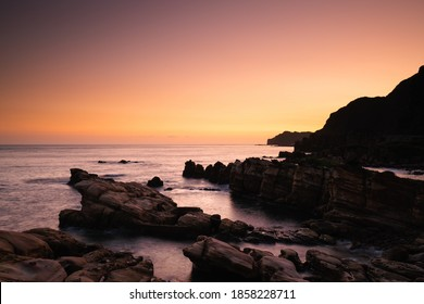 Dramatic dawning sky Law on peaceful sea water at the rocky beach in northeast Taiwan  Beautiful sunrise scenery of a rocky coast in rosy twilight Dramatic dawning sky reflected on peaceful sea water