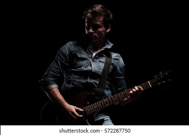 dramatic electric guitar player standing on black studio background