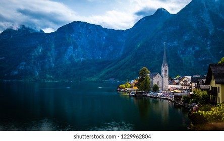Dramatic evening scenery of high rocky mountains and Hallstatt city at the wide lake