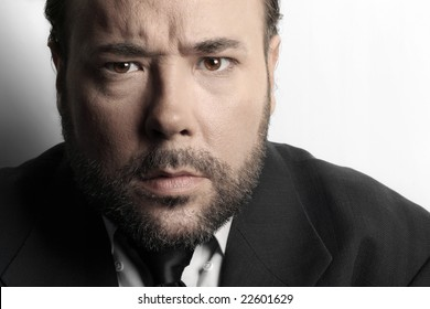 Dramatic extreme close-up of a very serious mature businessman in suit and tie against white background