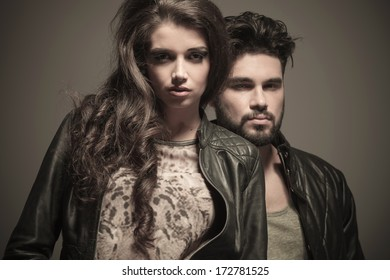 dramatic fashion couple in studio, man standing behind woman, looking at the camera
