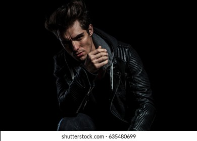 dramatic fashion model in leather jacket resting elbow on knee while seated on black background