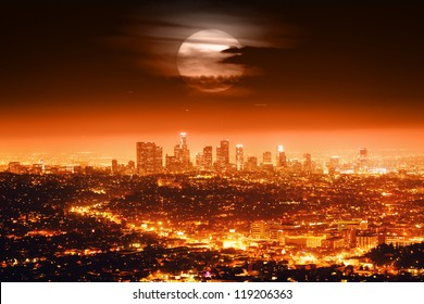 Dramatic full moon over Los Angeles skyline at night.