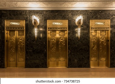 Dramatic golden elevators in fancy urban skyscraper building with relief sculptures and marble wall with lights and sconces