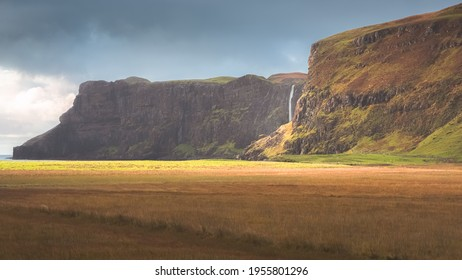 Dramatic golden light on the atmospheric coastal landscape at Talisker Bay and the seaside Talisker Waterfall on the Isle of Skye, Scotland