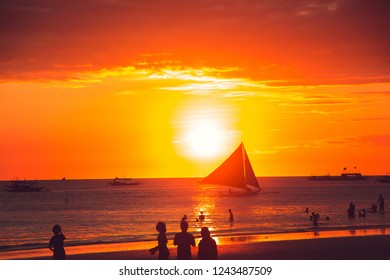 Dramatic golden sea sunset with sailboat. Summer time. Travel to Philippines. Luxury tropical vacation. Boracay paradise island. Nature background. Seascape view. Tourism concept. Water transport