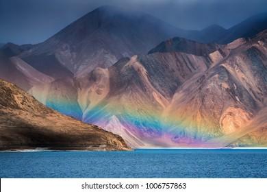 Dramatic Himalayas mountains and faded rainbow peeking over Pangong Tso lake at 4,350m above sea level.