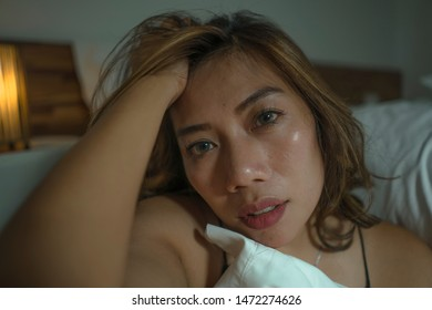 dramatic home lifestyle portrait of young beautiful sad and depressed Asian Indonesian woman in nightgown on bedroom floor by the bed feeling broken and lost suffering depression and anxiety