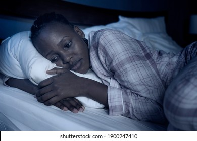 dramatic home portrait of young sick and depressed black afro American girl sitting on bed  upset and sleepless at night feeling overwhelmed suffering depression and anxiety problem