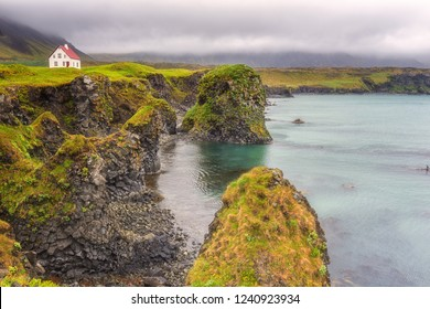 Dramatic icelandic landscape, lonely house on the volcanic cliffs seacoast, Arnarstapi, Snaefellsnes peninsula, Iceland