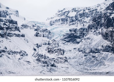 Dramatic icelandic landscape with snow covered rocky mountains with frozen glacier and warefalls.