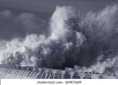 Dramatic image of beacon and south pier of Douro river mouth under heavy storm with big waves. Used infrared filter. Toned blue.