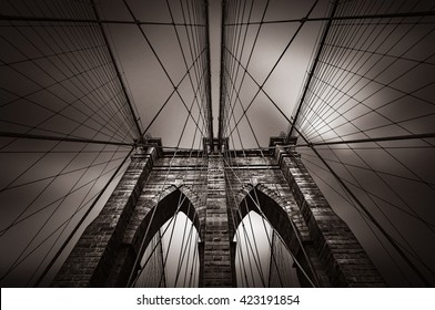 Dramatic image of Brooklyn bridge in NYC, USA. Old photo stylization, film grain added. Sepia toned