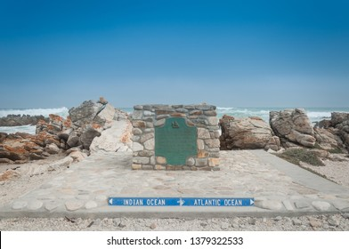 Dramatic image of the plaque marking Southern most point of the African continent, Cape Agulhas in South Africa, landmark marking the meeting point of the Atlantic and Indian Ocean with blue sky