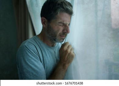 dramatic indoors portrait of mid adult man crying sad and depressed holding bedroom window curtain in despair at home feeling worried and overwhelmed suffering depression problem