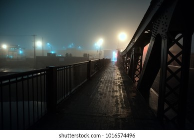 Dramatic industrial vintage river bridge scenery at night with illuminating fog in Chicago.