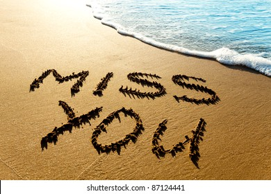 "Dramatic inscription ""Miss You"" on wet golden beach sand in sunset light"
