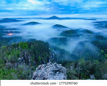 Dramatic landscape before sunrise in hilly landscape. View from exposed rock above vally