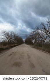 Dramatic landscape with a dirt road and cloudy sky. Vertical image may be used as background for a smartphone.