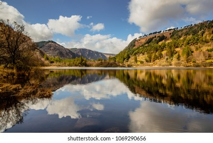 Dramatic landscape from the heart of Glendalough valley with the mountains and clouds reflecting in the water of the Lower lake. Irish Scenery. Blue sky. Wicklow National Park, Ireland