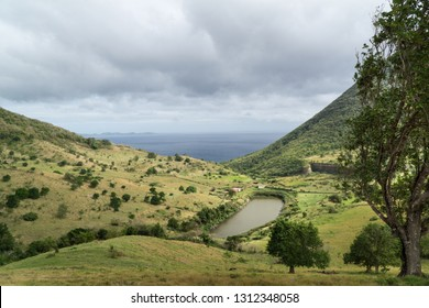 Dramatic landscape view of mountains, prairies & small lake with trees & the sea in background, under a grey rainy moody bad weather, with sun shine, Martinique, Caribbean creole Antilles, West Indies
