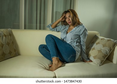 dramatic lifestyle portrait of young beautiful sad and depressed woman thoughtful and confused at home couch feeling broken heart suffering depression crisis and anxiety problem