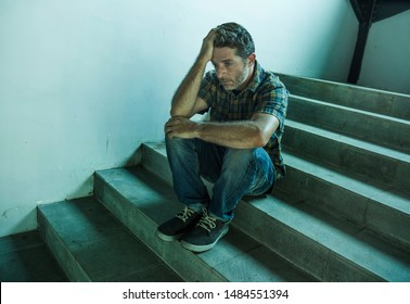 dramatic lifestyle portrait of young depressed and sad man sitting alone outdoors on dark street staircase suffering depression problem and anxiety crisis crying desperate feeling miserable