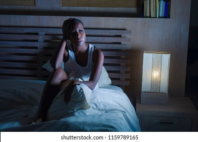 dramatic lifestyle portrait of young sad and depressed black african American woman on bed sleepless suffering headache insomnia sleeping disorder and anxiety problem feeling unwell and upset
