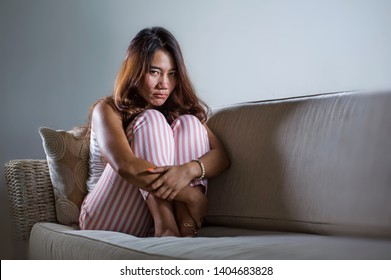 dramatic lifestyle portrait of young sad and depressed Asian Indonesian woman stting at home couch crying frustrated and upset suffering stress and depression after breakup