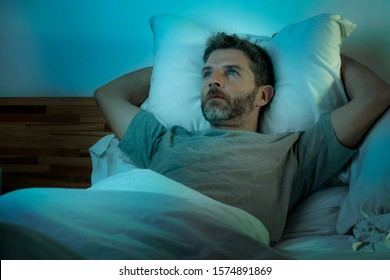 dramatic lifestyle portrait of young sad and depressed man lying thoughtful and pensive on bed looking away feeling lost thinking suffering some problem in sadness emotion and depression concept