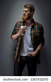 Dramatic light concept photo of confident young bearded man holding cup of coffee Side view portrait of male model with ginger hair