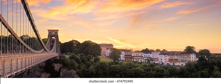 Dramatic light over the historic Clifton suspension bridge with housing on the other side of the gorge, Bristol Ciity, England.