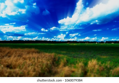 Dramatic light rays over summer field bokeh backdrop