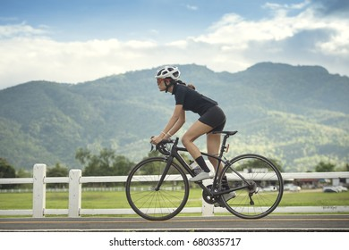 Dramatic lighting with female cyclist cycling on track with road bicycle speed and sprint and sport wellness concept