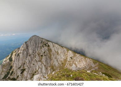 Dramatic limestone mountain scenery with storm clouds, fog and trekking path