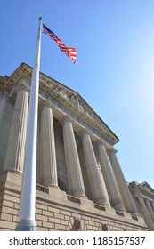 Dramatic low angle of a neoclassic United States governmental building in the Federal Triangle of Washington, D.C.  Six Doric columns form the portico. The American flag flies in the foreground.