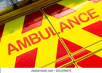 Dramatic low angled view of AMBULANCE sign on red & yellow NHS medical vehicle.